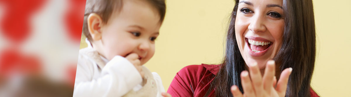 Nursery staff member clapping for child