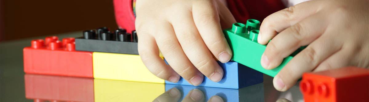 Close up of young hands playing with building blocks