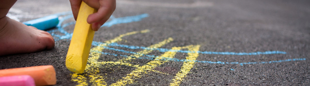 Child drawing with chalks on playground floor